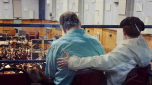 Two people from behind, with orchestra beyond